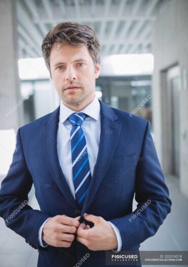 focused_225316018-stock-photo-portrait-confident-businessman-standing-office
